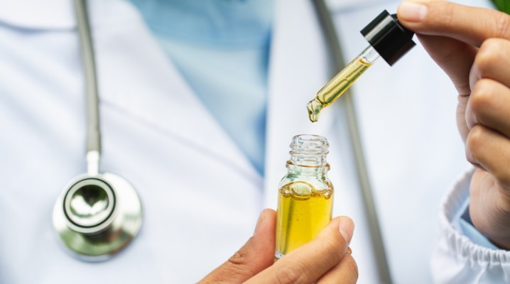hemp-oil-doctor-holding-a-bottle-of-hemp-oil-medical-marijuana-picture-id1158309980